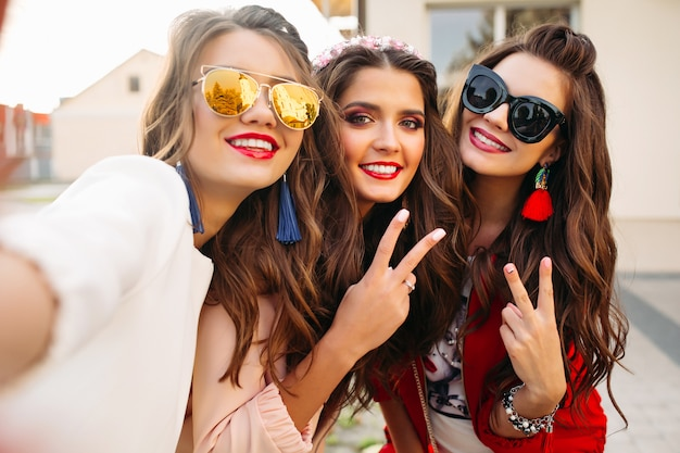 Beautiful girlfriends in sunglasses showing peace signs Premium Photo