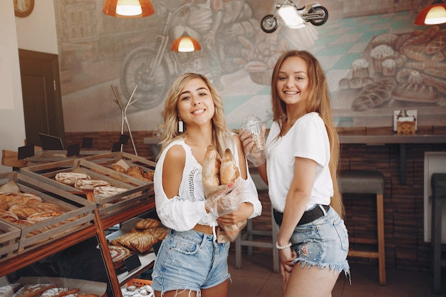 Beautiful girls buys buns at the bakery Free Photo