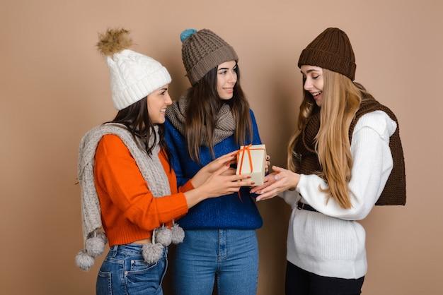 Beautiful girls give a girlfriend a holiday gift Premium Photo