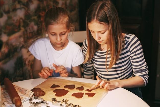 Красивые девушки на домашней кухне за столом вырезали из теста печенье в форме сердца Premium Фотографии