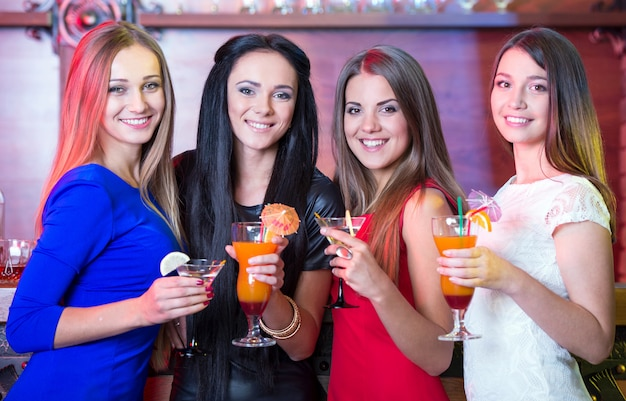 Beautiful girls sit at bar in their hands holding cocktails. Premium Photo
