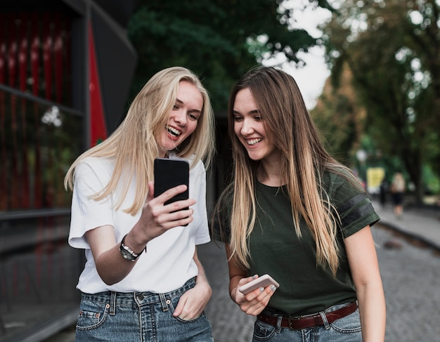 Beautiful girls taking a selfie with phone Free Photo
