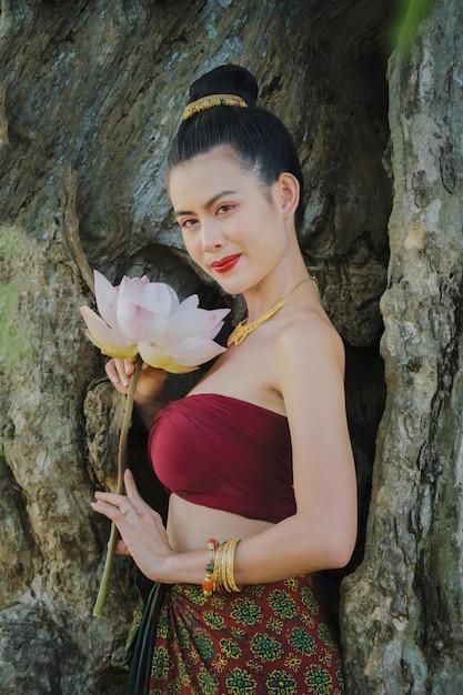 Beautiful girls in traditional costume.beautiful young woman in traditional dress costume with hands holding pink of lotus. Premium Photo