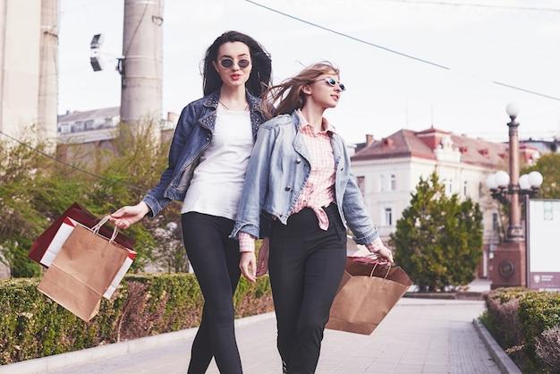 ショッピングモールで歩いて買い物袋を持つ美しい女の子。 無料写真
