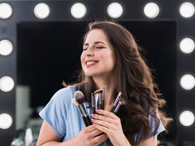 Beautiful glad woman makeup stylist with brushes in hands Free Photo