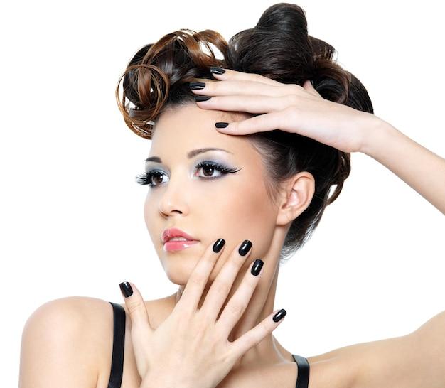 Bella donna glamour con acconciatura alla moda e unghie nere. trucco occhi alla moda Foto Gratuite