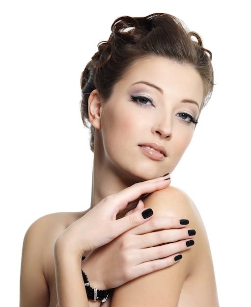 Красивая гламурная молодая женщина с черными ногтями и стильной прической позирует на белом Бесплатные Фотографии