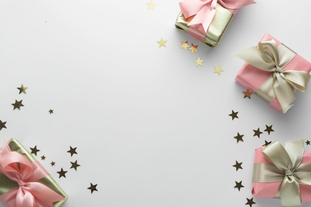 Beautiful golden gifts glitter conffeti pink bows ribbon on white. christmas, party, birthday . celebrate shinny surprise boxes copyspace. creative flat lay top view. Premium Photo