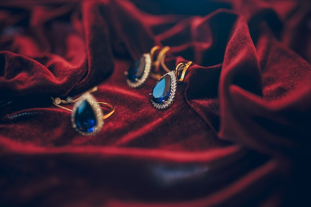 Beautiful golden jewelry with jem on red velvet background Premium Photo
