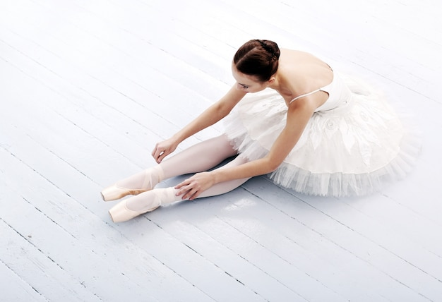 Beautiful and gorgeous ballerina sitting on the floor Free Photo