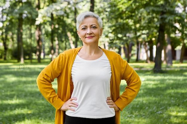Bella donna senior dai capelli grigi in cardigan giallo e maglietta bianca in posa nel parco verde estivo, tenendo le mani sulla sua vita, facendo esercizi fisici, con un sorriso sicuro Foto Gratuite