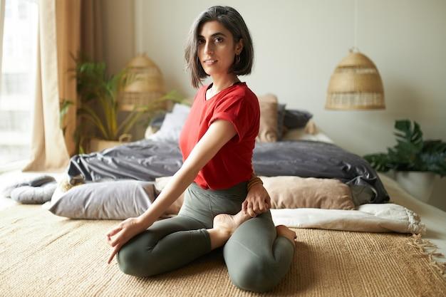 물고기 자세 또는 Ardha Matsyendrasana의 절반 제왕에 앉아 Activewear에 아름 다운 회색 머리 젊은 여자 무료 사진