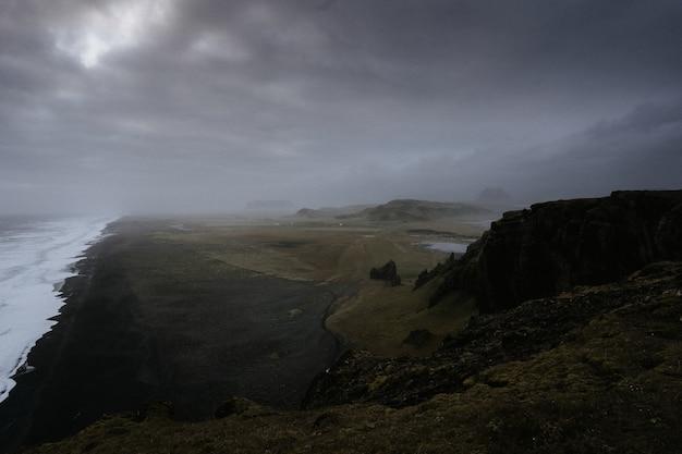 霧に包まれた高山に囲まれた湖のある美しい緑の風景 無料写真