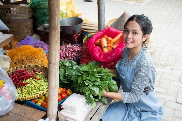 Красивая женщина-овощерезка укладывает шпинат для овощного прилавка на традиционном рынке Premium Фотографии