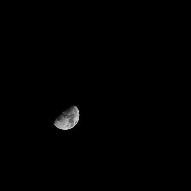 真っ暗な暗い空に美しい灰色の半月 無料写真