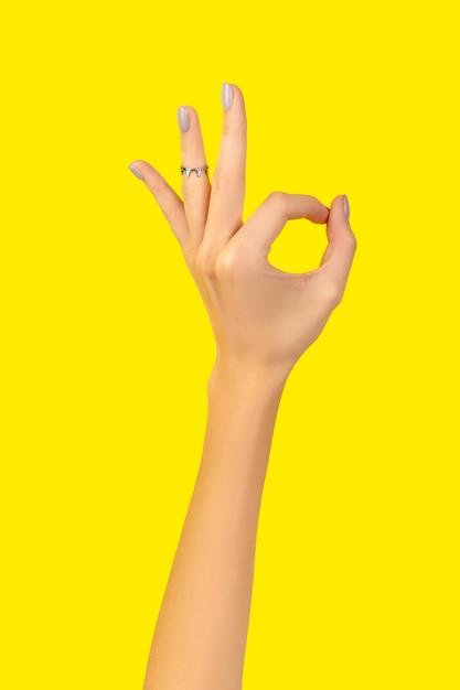 노란색 괜찮아 제스처와 아름 다운 손질 된 여자 손 프리미엄 사진