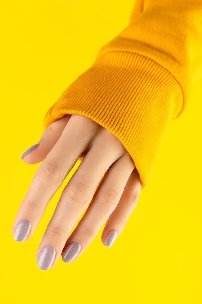 노란색에 유행 네일 디자인으로 아름 다운 손질 된 여자 손 프리미엄 사진
