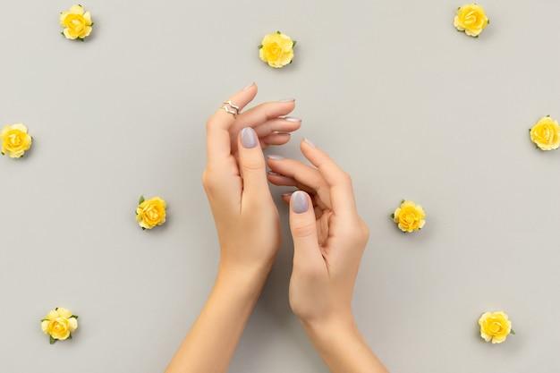 회색에 최소한의 네일 디자인으로 아름다운 손질 된 여자 손 프리미엄 사진