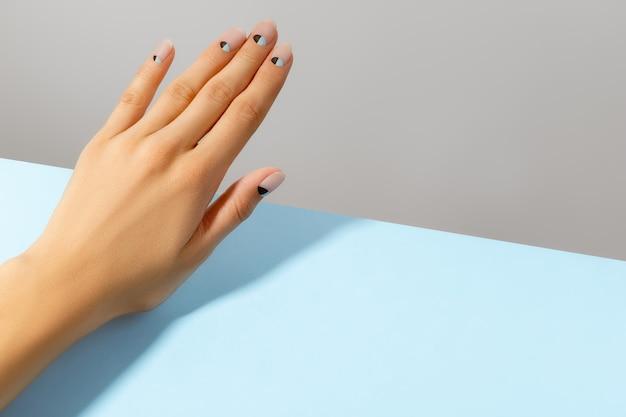 누드와 블루 매트 네일 디자인으로 아름다운 손질 된 여자 손. 매니큐어 페디큐어 미용실 개념. 프리미엄 사진