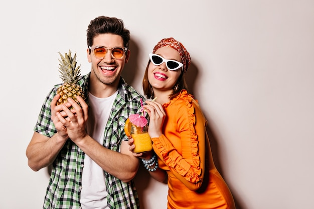 Красивый парень и девушка в солнечных очках и яркой летней одежде улыбаются и наслаждаются коктейлем и ананасом. Бесплатные Фотографии
