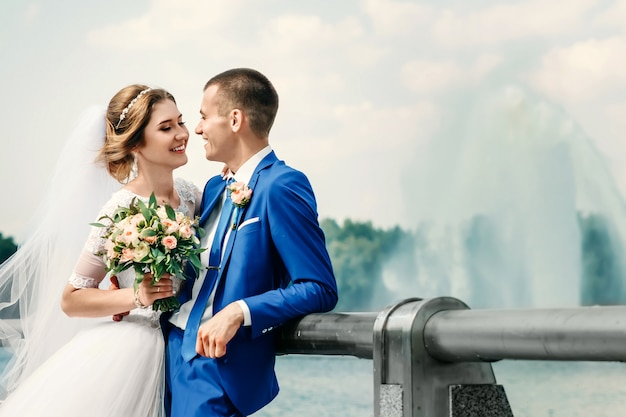Beautiful guy and girl, bride in a white wedding dress, groom in a classic blue suit against a nature background. wedding, family creation. Premium Photo