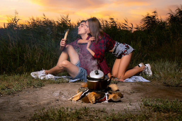 A beautiful guy and a girl in red checkered shirts, blowing on a smoking stick with which smoke is coming... Premium Photo
