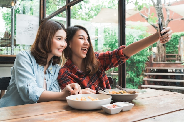 Beautiful happy asian women lesbian lgbt couple sitting each side eating a plate of italian seafood Free Photo