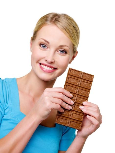 彼女の顔の近くのチョコレートの甘い黒いバーを保持している幸せな金髪美人 無料写真