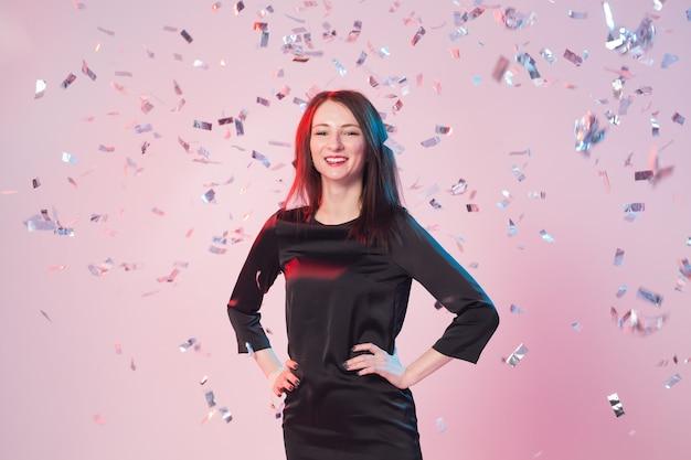 아름 다운 행복 한 갈색 머리 여자 웃 고 떨어지는 색종이 함께 포즈. 파티 컨셉 프리미엄 사진