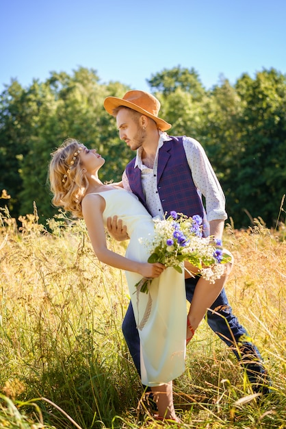 Beautiful happy couple dancing in a field in summer on a sunny day. Premium Photo