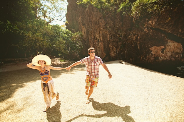 Beautiful happy couple holding hands, walking on the beach with mountains on a sunny day, outdoors. a girl in a hat and a guy on vacation in a tropical country. lifestyle travel and tourism, honeymoon Premium Photo