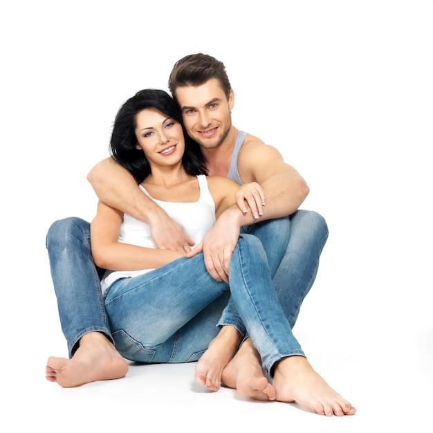 ブルージーンズと白いアンダーシャツに身を包んだ白いスペースで恋に美しい幸せなカップル 無料写真