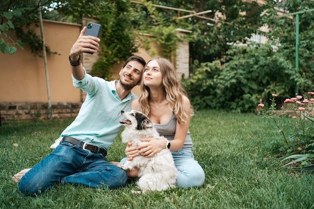 Belle coppie felici che fanno selfie con il loro adorabile cane nel cortile mentre era seduto sull'erba Foto Gratuite