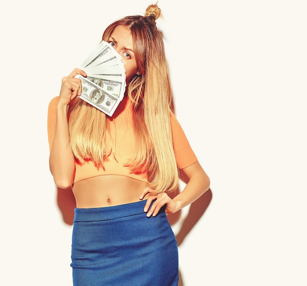 Beautiful happy cute smiling blonde woman girl in casual colorful hipster summer clothes with no makeup holding dollar banknotes Free Photo