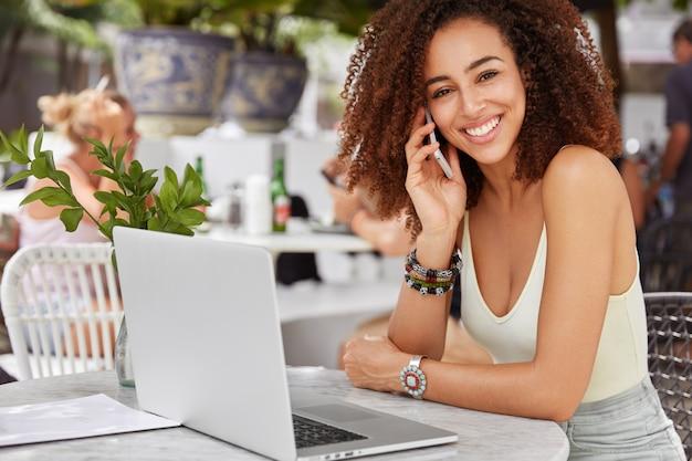 Красивая счастливая темнокожая женщина-оператор вызова для получения консультации, использует электронные устройства, отдыхает в уютном кафе. Бесплатные Фотографии