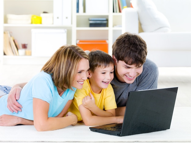 Beautiful happy family with child looking at laptop with cheerful smile - indoors Free Photo