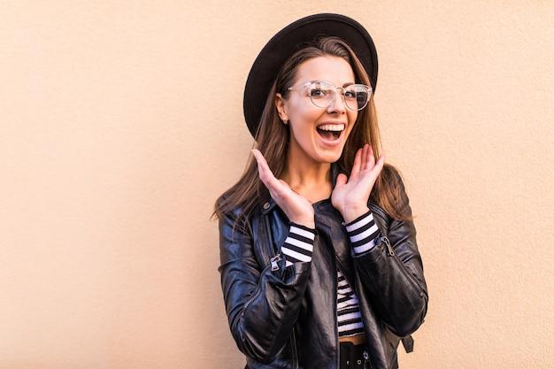 Bella ragazza felice di modo in giacca di pelle e cappello nero isolato sul muro giallo chiaro Foto Gratuite