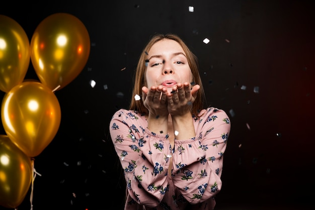 Beautiful happy girl blowing a kiss and golden balloons Free Photo