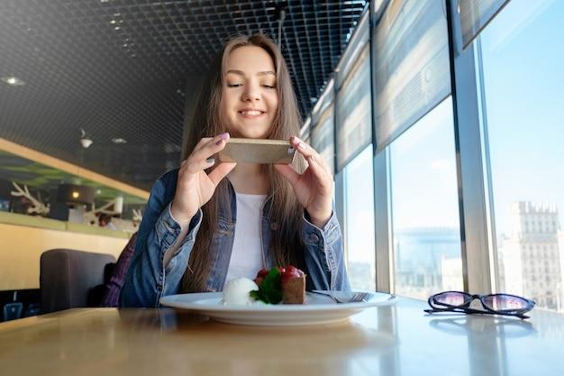 아름 다운 행복 소녀 카페에서 음식 사진, 테이블에 라떼, 디저트 아이스크림 초콜릿 케이크 체리 민트 프리미엄 사진