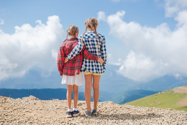 Beautiful happy little girls in mountains in the of fog Premium Photo
