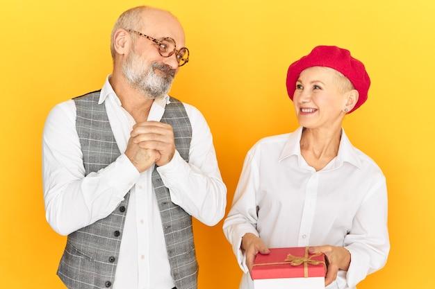 Bella donna matura felice in berretto rosso che riceve il regalo di compleanno dal marito che si congratula con lei con tutto il cuore. uomo colpevole e triste che ripara la sua colpa, conquistando la moglie con un regalo Foto Gratuite
