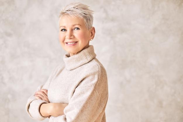 Красивая счастливая пенсионерка, одетая в уютный свитер и короткую прическу Бесплатные Фотографии
