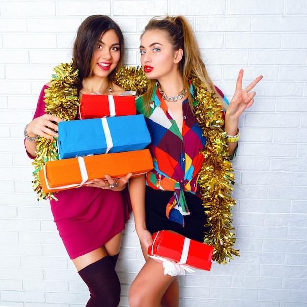 파티 선물 및 선물을 들고 아름 다운 행복 미소 가장 친한 친구. 트렌디 한 옷과 황금빛 반짝이를 입고 무료 사진