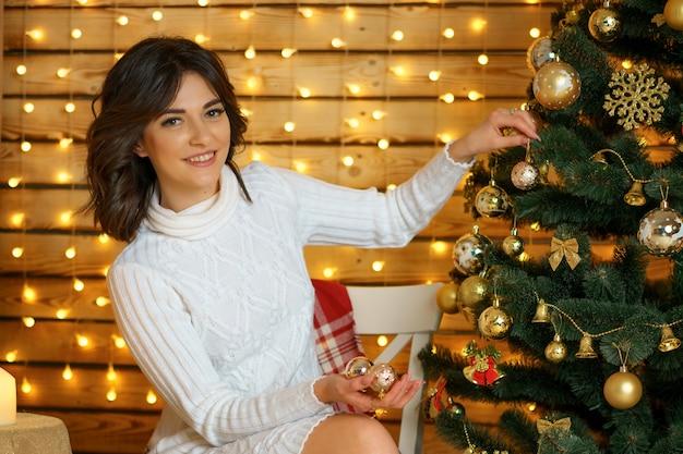 Beautiful happy woman dresses up christmas tree Premium Photo