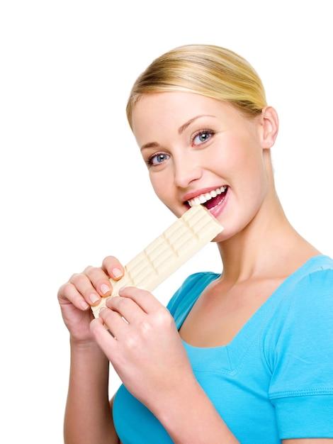 La bella donna felice mangia il cioccolato poroso bianco dolce - isolato su bianco Foto Gratuite