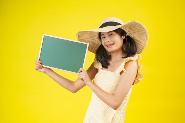 A beautiful, happy woman wearing a big hat and holding a green board on a yellow . Free Photo