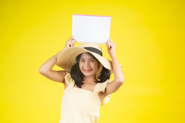 A beautiful, happy woman wearing a big hat and holding a white book on a yellow . Free Photo