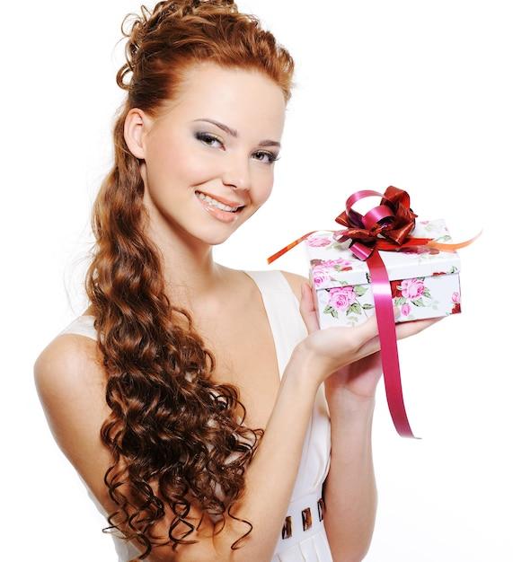 白い背景の上にプレゼントを保持している美しい幸せな若い女性 無料写真