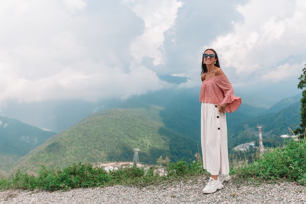 Beautiful happy young woman in mountains in the background of fog Premium Photo