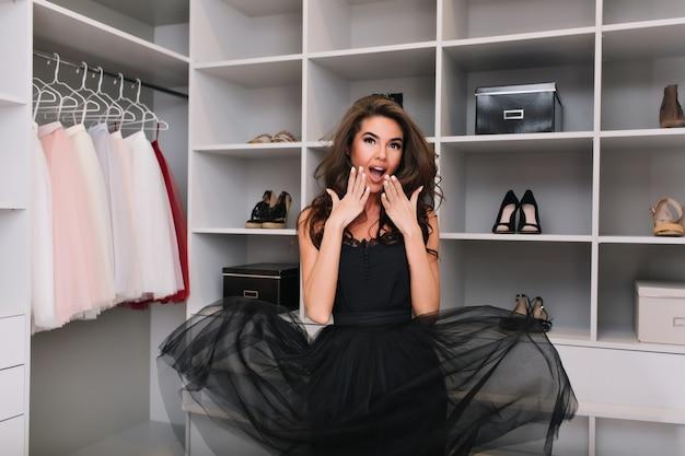 Красивая счастливая молодая женщина с длинными каштановыми вьющимися волосами приятно удивила, шокировала столько красивой одежды в роскошном гардеробе. модная модель имеет элегантный вид в стильном черном платье. Бесплатные Фотографии